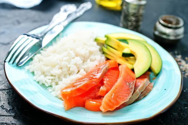 Порция диетического блюда. Ингредиенты: лосось, авокадо, рис отварной.