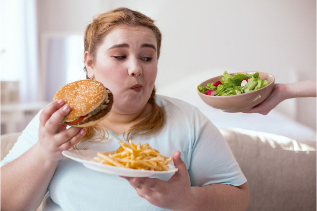Молодая толстая девушка ест чизбургер с картошкой фри.