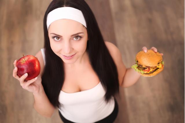 Молодая девушка держит в руках яблоко и чизбургер.