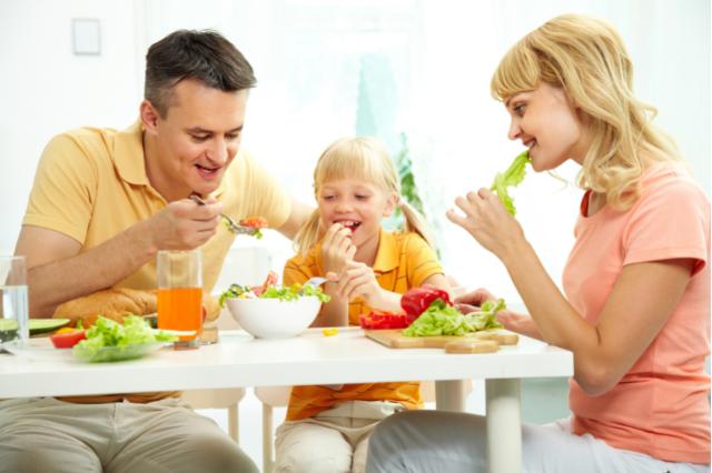 Молодая семья завтракает полезными продуктами питания.