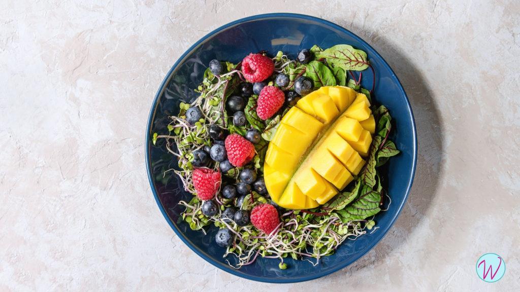 Пророщенная зеленая гречка с ягодами и фруктами на тарелке.